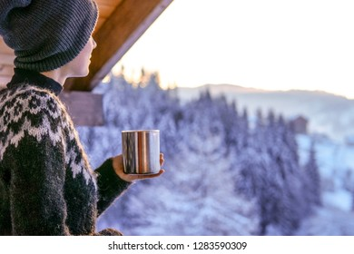 Young woman drinking coffee with a view of the winter mountain landscape