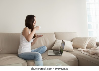 Young woman drinking coffee while sitting comfortably at home sofa, happy teen relaxing with laptop computer, relaxed girl enjoying spending time alone watching series online on pleasant weekend