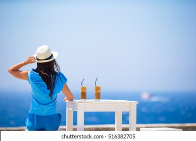 Young woman drinking cold coffee enjoying sea view. Beautiful woman relax during exotic vacation on the beach enjoying frappe