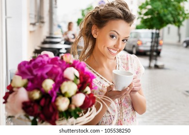 A young woman are drinking espresso. Holding a cup of espresso. Outdoors