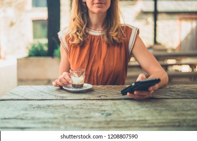 A young woman is drinking espresso and using her smartphone at a table outside