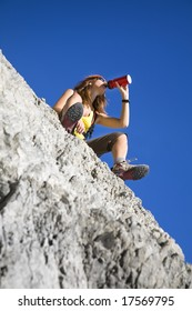 young woman drinking from flask on top of the mountain