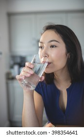 Young woman drinking a glass of water in kitchen at home