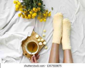 Young woman drinking herbal tea with yellow candies wearing yellow cozy socks in cozy bed with yellow spring flowers in the morning or at holidays