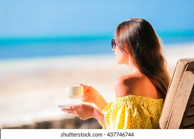 Young woman drinking hot coffee enjoying beach view. Beautiful woman relax during exotic vacation on the beach enjoying sweet coffee