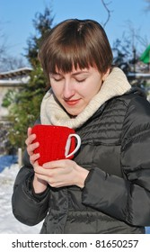 Young woman drinking hot tea outdoors in snowy garden