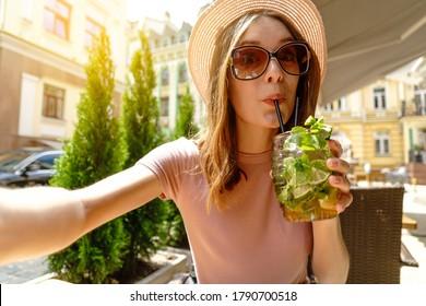 Junge Frau trinkt Mojito-Cocktail auf der Cafetterrasse bei heißem Sommertag und macht Selfie-Shooting