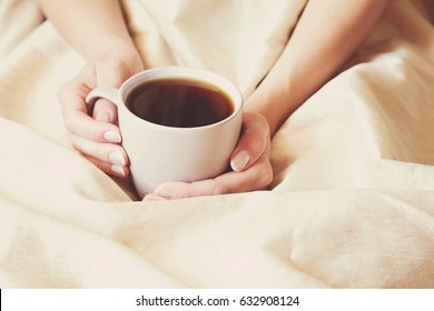 Young woman drinking morning coffee in the bed. Surprise from beloved man. Hands holding a mug.