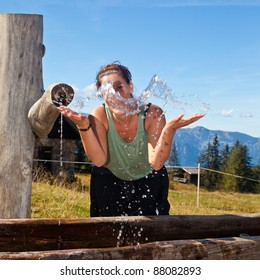 Young woman drinking and playing with water in the alps.