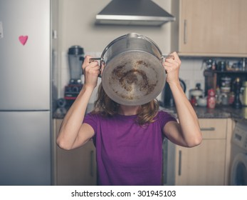 A young woman is drinking from a pot in a kitchen