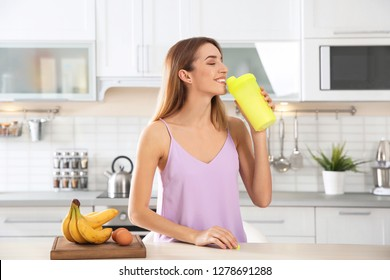 Young woman drinking protein shake near table with ingredients in kitchen