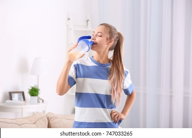 Young woman drinking protein shake indoors