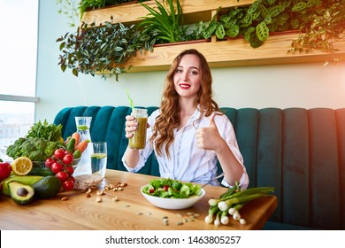 Young woman drinking smoothie in the beautiful interior with green flowers on the background and fresh fruits and vegetables. Healthy eating concept. Vegan meal and detox menu