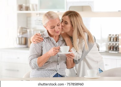 Young woman drinking tea with elderly mother at home
