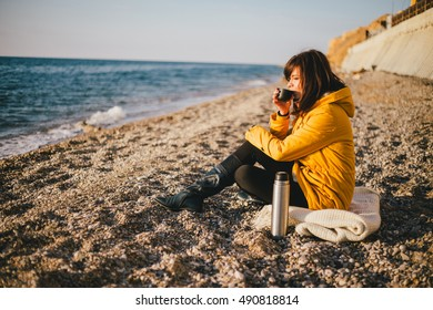 Young woman drinking tea from her thermos, enjoying autumn evening by the sea
