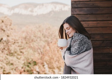 Young woman drinking tea on cozy balcony of a wooden country house.