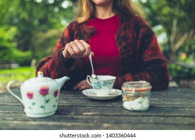 A young woman is drinking tea outdoors in a park and is stirring her cup