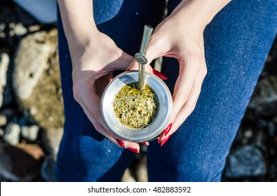 Young woman drinking traditional Argentinian yerba mate tea from a calabash gourd with bombilla stick on a sunny day
