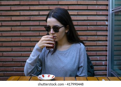 Young woman drinking traditional Turkish tea