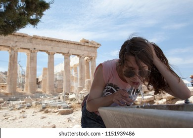 young woman drinking water in acropolis