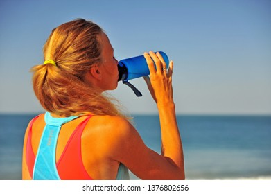 Young woman drinking water after workout outdoors