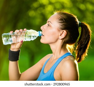 Young woman drinking water after fitness exercise. Cold drink  at summer green park. Outdoor sport