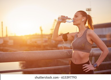 Young woman drinking water after running