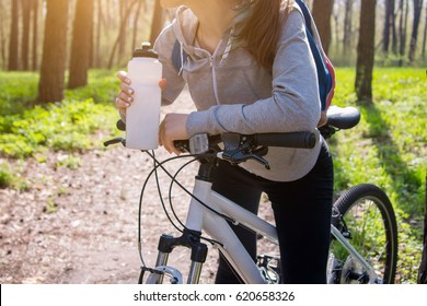 Young woman drinking water after riding a bicycle in the forest at sunset