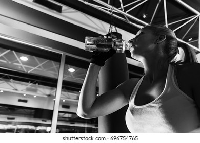 Young woman drinking water after a gym session. Shot of a woman drinking water while sitting after a workout. fitness workout sport and lifestyle. Black and white fitness women