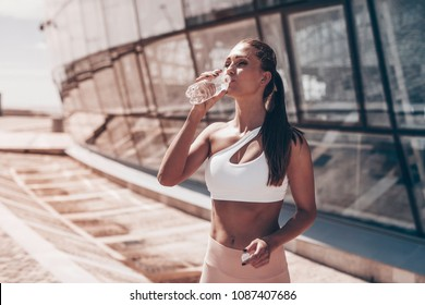 Young woman drinking water from bottle after run. Street workout.