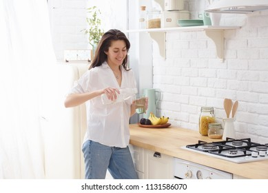 Young woman drinking water from glass in the kitchen.