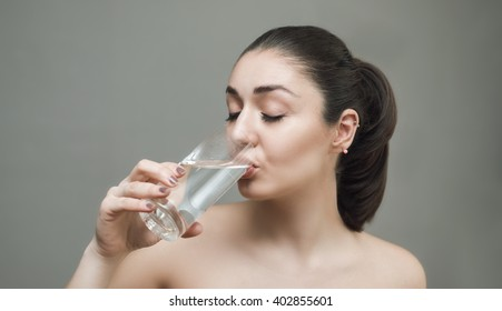 Young woman drinking water from the glass in gray background