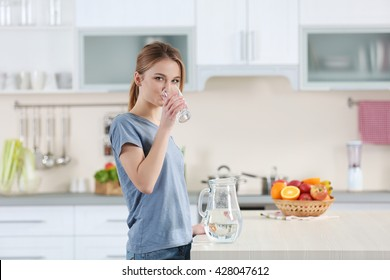 Young woman drinking water from glass in the kitchen