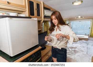 young woman drinking water and living in a camper RV van motorhome