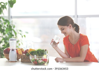 Young woman drinking water near table with fruits and vegetables in the kitchen