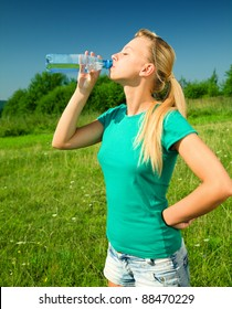 Young woman is drinking water from plastic bottle outdoors