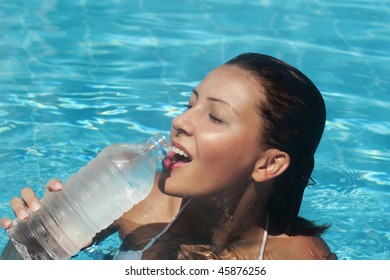 young woman drinking water in a turquoise pool