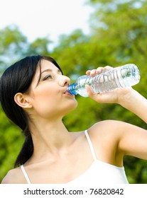 Young woman drinking water at workout, outdoors