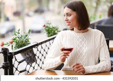 Young woman drinking wine in cafe