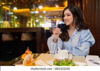 young woman drinking wine in the restaurant