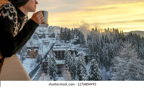 Young woman drinknig coffee with a view of the winter mountain village landscape. Winter traveler in ski resort.