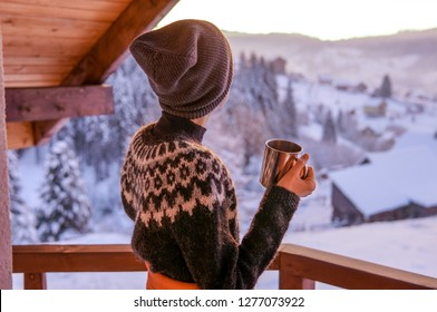 Young woman drinknig coffee with a view of the winter mountain landscape