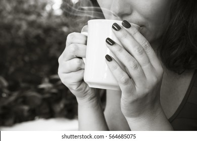 Young woman drinks coffee from white cup. Close-up black and white photo, selective focus on hands
