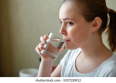 Young woman drinks glass of pure water in morning after waking up. Happy teen girl maintains water balance for body health by drinking a transparent cup of clean water