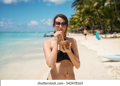 Young woman drinks refreshing coconut cocktail at tropical beach.