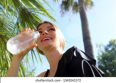 The young woman drinks water from a bottle. Concept of a healthy life. A girl sitting on a sunny day under a palm tree