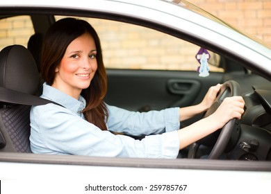 young woman drinving her car wearing her seatbelt.