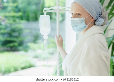 Young woman with drip standing by the hospital window