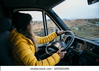 Young woman drive camping van on epic mountain road. Female adventurer travel in remote locations to camping destination. Vanlife lifestyle for urban travellers