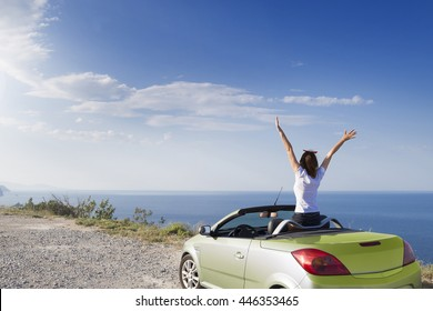 Young woman drive a car on the beach.